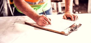 man working with pen and clipboard